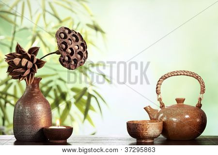 Teapot and cup on table with bamboo leaves.
