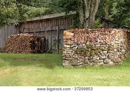 Woodpile On Stone Wall
