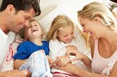 picture of tickling  - Family Relaxing Together In Bed - JPG