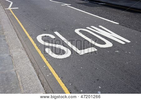 Close up of road marking saying Slow in London, UK