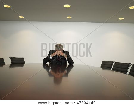 Stressed out businessman with hands clasped sitting at table in conference room