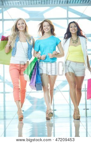 Portrait of three glamorous girlfriends with paperbags walking down trade center