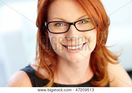 Close-up shot of a wonderful red-haired woman looking at camera