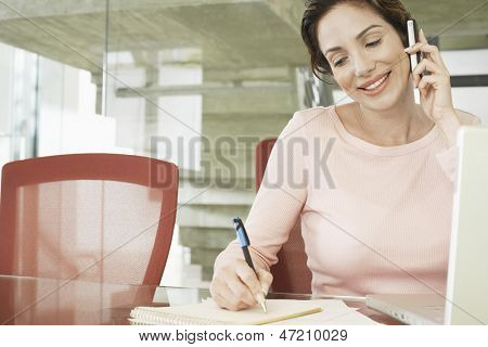 Happy young businesswoman using mobile phone while writing on notepad in office