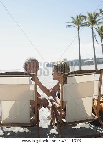 Rear view of romantic senior couple sitting on deckchairs at sunny beach