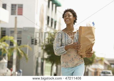 Saco de compras jovem mulher carregando a sorrir enquanto caminhava na rua