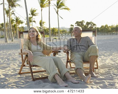 Full length of happy senior couple relaxing on deckchairs at tropical beach