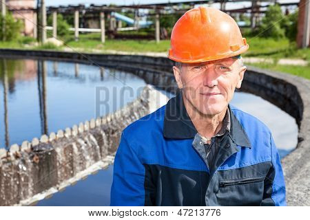 Caucasian Senior Manual Worker Sitting Near Water Filtration Unit. Copyspace