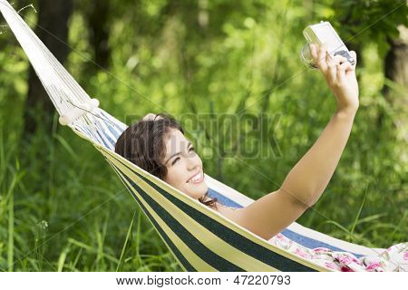 Young woman lying in a hammock in garden doing snapshot.