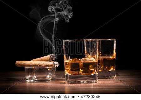 Whiskey drinks with cigars on wooden table