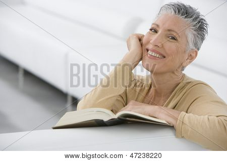 Portrait of smiling senior woman with book on sofa at home