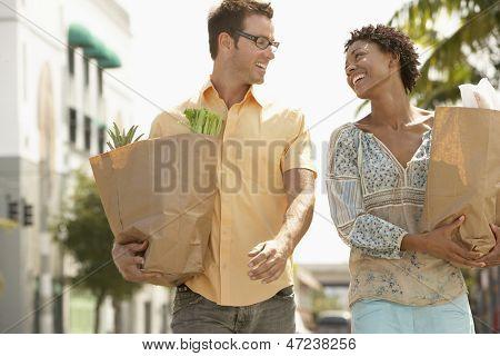 Casal jovem multiétnico feliz com compras, caminhar ao ar livre