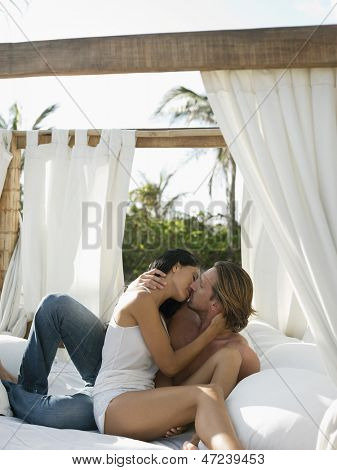 Passionate young couple kissing on four-poster bed outdoors