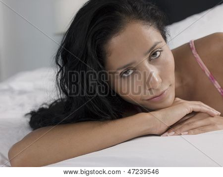 Closeup portrait of sensuous young woman relaxing in bed