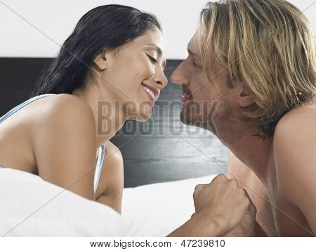 Romantic young couple about to kiss on bed in hotel room