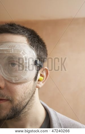 Closeup of man wearing protective eyegoggles and earplugs