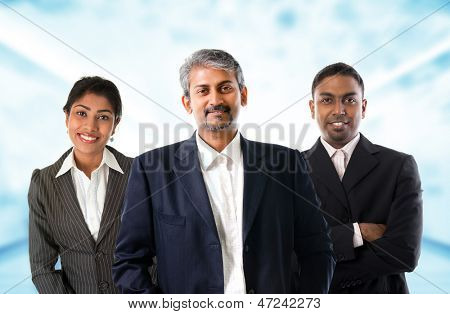 Indian business team.  Asian Indian businessmen and businesswoman in group. Teamwork concept standing inside office building. Good looking Indian model.