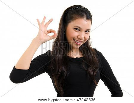 Pretty young woman showing okay hand sign with great smile standing isolated on white background. Beautiful mixed race Caucasian Southeast Asian woman model.