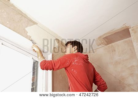 Low angle view of man scraping paint off wall in unrenovated room