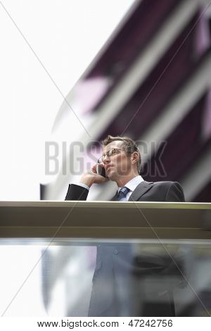 Low angle view of businessman communicating on mobile phone in front of railing