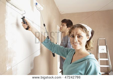 Portrait of woman and man painting wall with paint rollers
