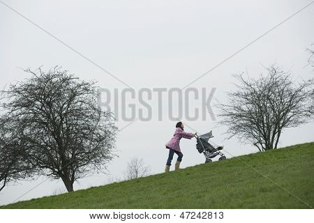 Full length of young mother pushing stroller uphill in park