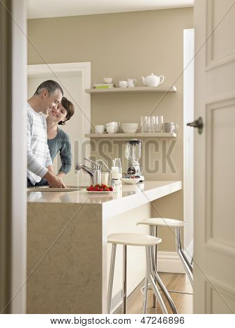Happy couple standing at kitchen counter seen through open door