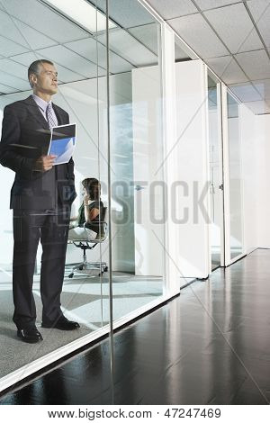Full length of thoughtful middle aged businessman standing against glass wall in office