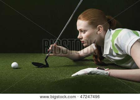 Side view of young woman reclining on floor holding golf club looking at golf ball