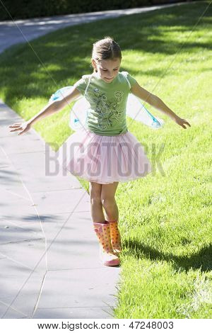 Full length of girl wearing fairy wings and tutu balancing on edge of path at park