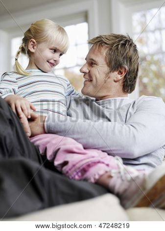 Cute little daughter sitting on father's lap while looking at each other at home