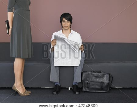 Low section of businesswoman standing by businessman reading newspaper in lobby