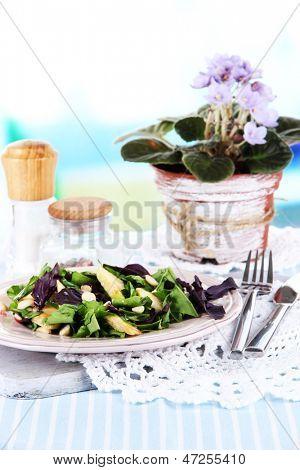 Light salad on plate on table on room background