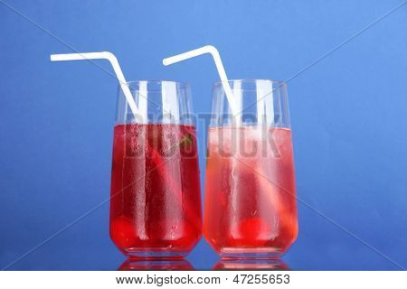 Two cherry cocktails with ice on blue background