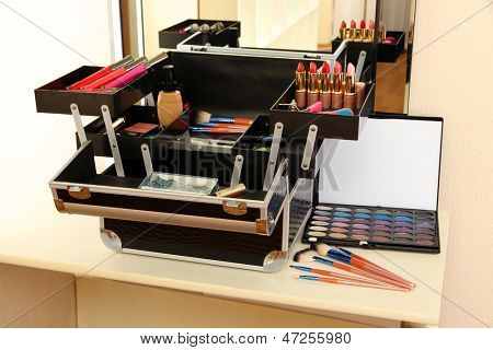 Open case with cosmetics on table near mirror