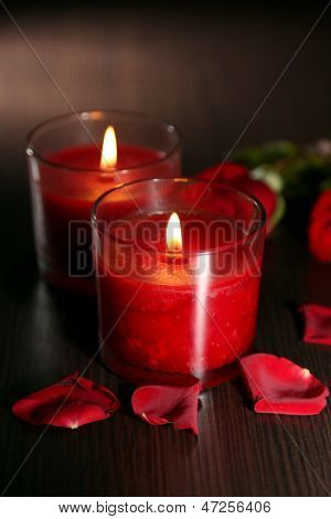 Beautiful romantic red candles with flower petals on dark wooden background