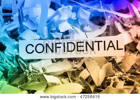 scraps of paper with the word confidential, symbolic photo for data destruction, bank secrecy and confidentiality