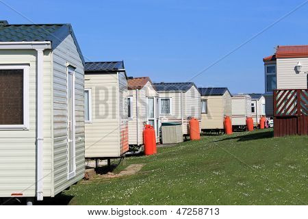 Row of caravans in trailer park, summer scene.