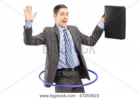 Young businessman in suit holding a briefcase and dancing with a hula hoop isolated on white background