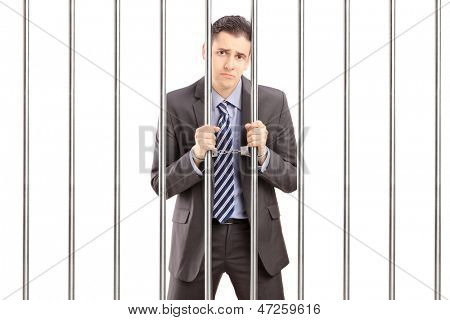 Sad handcuffed businessman in suit posing in jail and holding bars, isolated on white background