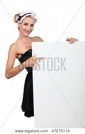 Woman in a French maid's outfit pointing at a blank board ready for text