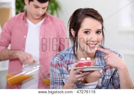 girl eating strawberry gateau with boyfriend in background