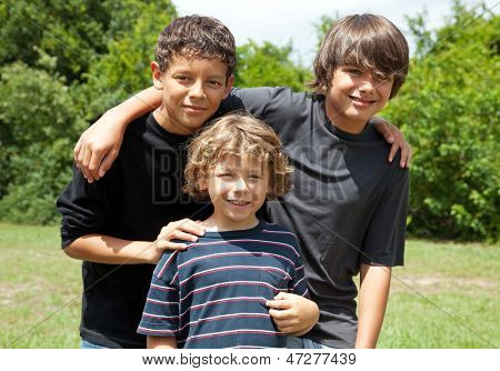 Three adorable boys, two adolescent friends and one little brother smiling. Diversity.   The two brothers are mixed race.