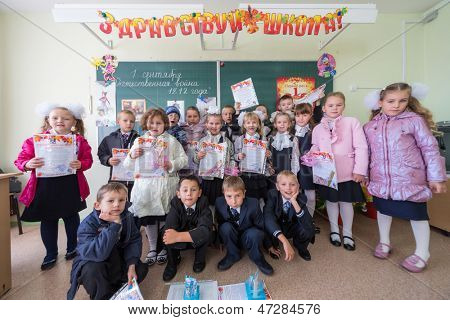 MOSCOW - SEP 1: Dressed first-graders with gifts in hands in a classroom of School No.1349 on September 1, 2012 in Moscow, Russia.