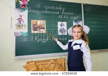 MOSCOW - SEP 1: Little school girl Anya 7 years old stands at the blackboard with a pointer in School No. 1349 on the first day of school on September 1, 2012 in Moscow, Russia.
