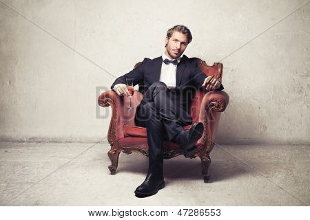 attractive young man sitting on an armchair