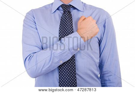 Businessman taking oath with fist over heart.