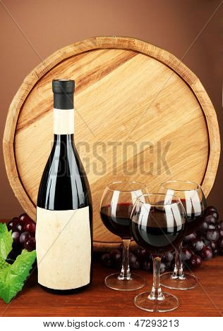 Composition of wine, wooden barrel and  grape, on brown background