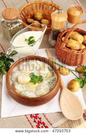 Tender young potatoes with sour cream and herbs in wooden bowl on tablecloth close-up