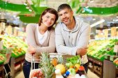 Image of happy couple with cart full of products looking at camera in supermarket